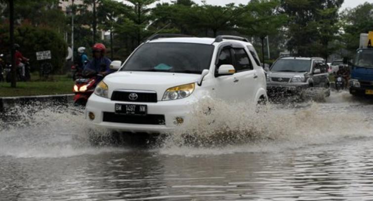 Gambar menunjukkan Mobil warna putih sedang melewati genangan air