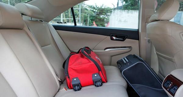 Gambar menunjukkan sebuah tas warna merah yang diletakkan di atas jok mobil