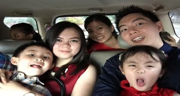Gambar ini menunjukkan sebuah keluarga sedang foto-foto di dalam mobil