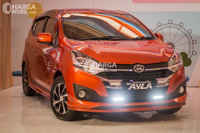 Gambar mobil Daihatsu Ayla 2017 berwarna orange dilihat dari sisi depan