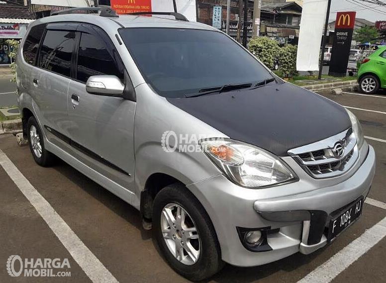 Gambar ini menunjukkan sebuah mobil daihatsu Xenia warna silver dengan kap mesin warna hitam sedang parkir
