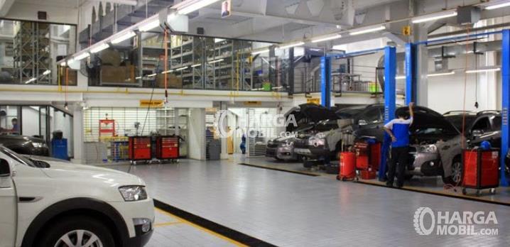 Gambar ini menunjukkan bengkel resmi Daihatsu dengan beberapa Mobil warna silver sedang diperiksa
