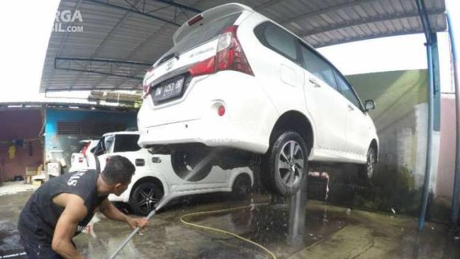Gambar ini menunjukkan sebuah mobil warna putih sedang diangkat dan dicuci bagian bawah mobil