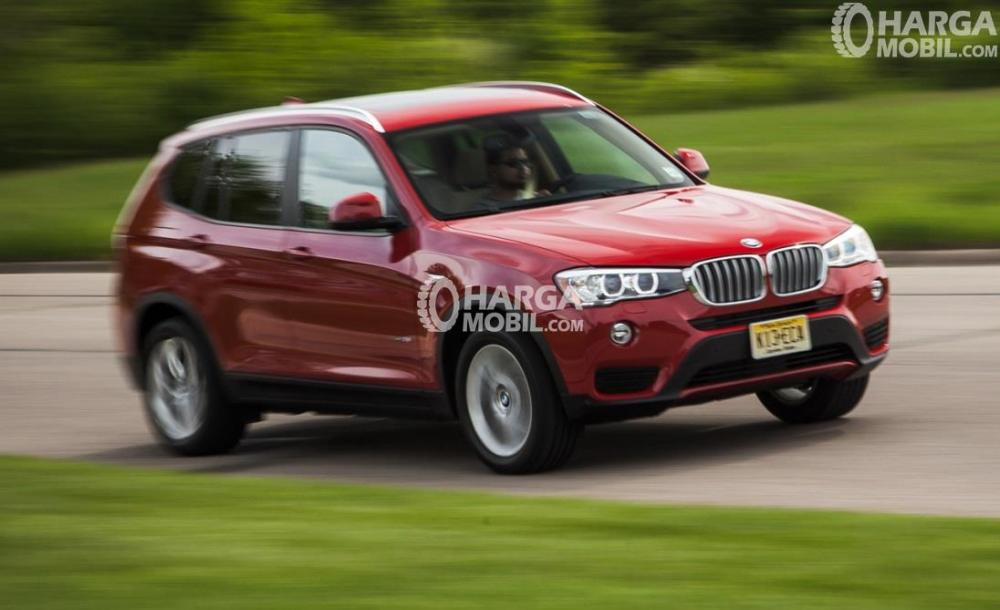 Gambar mobil BMW X3 2016 berwarna merah dilihat dari sisi depan sedang berlaju di jalan