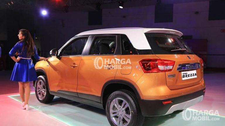 Gambar mobil Suzuki Vitara Breeza 2018 berwarna orange dilihat dari sisi belakang dan di sebelah kanan ada sebuah model yang cantik berpakaian biru