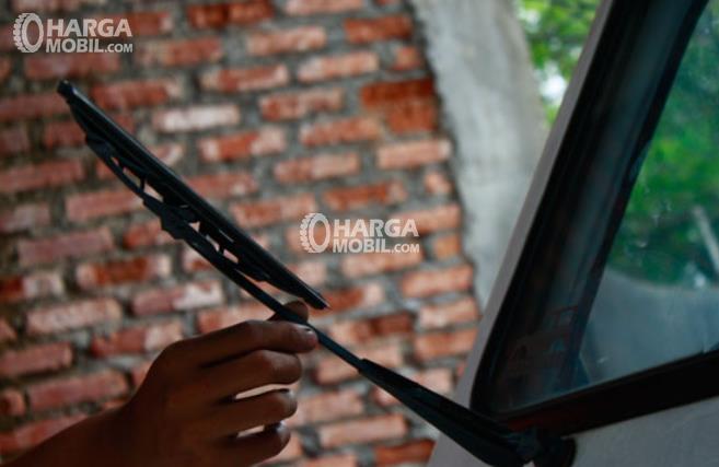 Gambar ini menunjukkan sebuah tangan memegang tangkai wiper dan menaikkannya