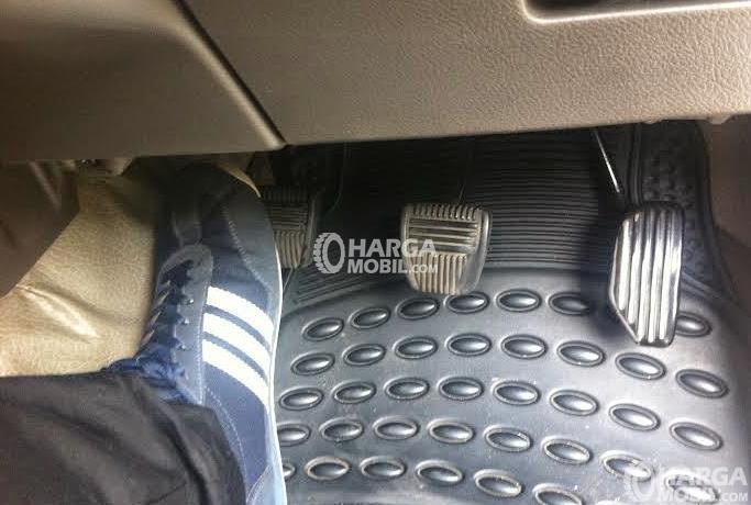 Gambar ini menunjukkan sebuah kaki memakai sepatu menginjak pedal kopling pada mobil