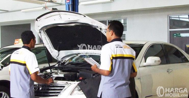 Gambar ini menunjukkan 2 orang mekanik sedang melakukan pengecekan pada mesin mobil warna putih
