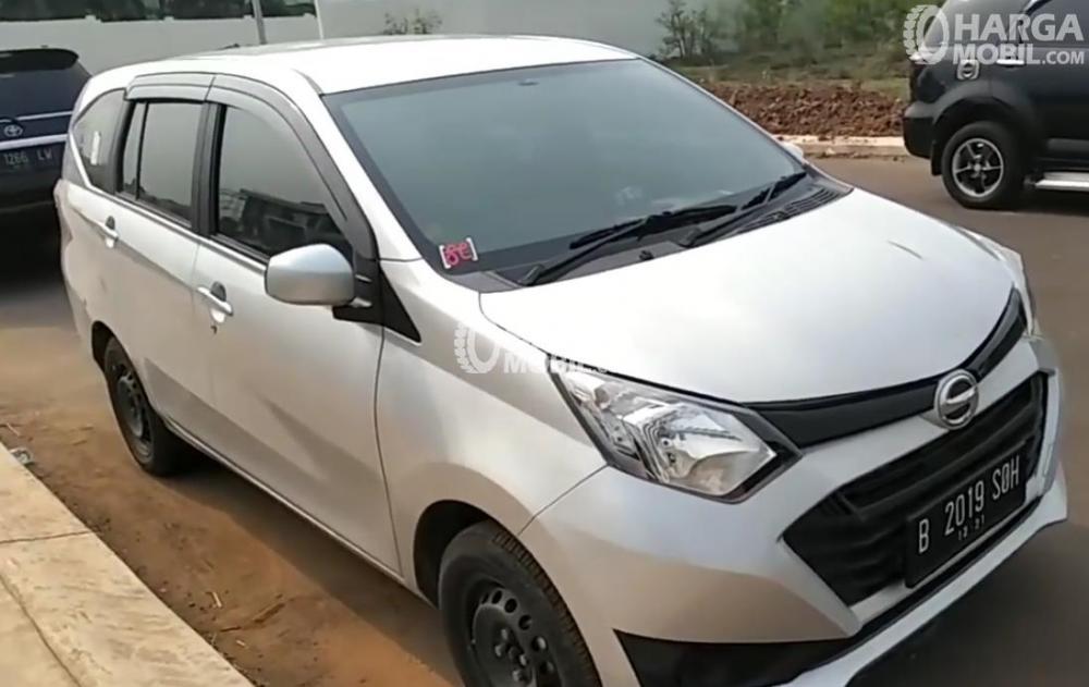 Gambar ini menunjukkan Daihtsu Sigra warna putih tampak depan dan terdapat Mobil lain di belakangnya