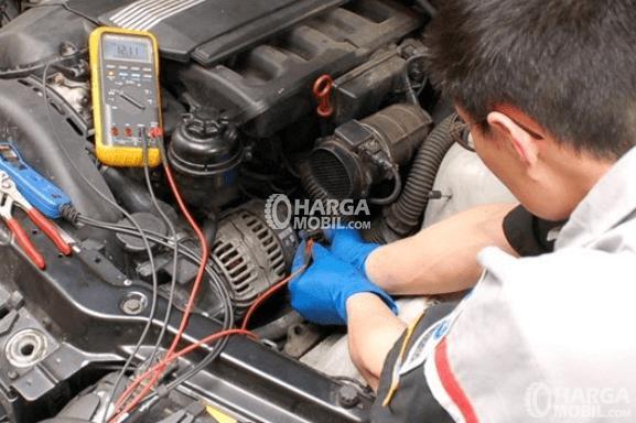 Gambar ini menunjukkan seorang mekanik bengkel sedang melakukan pemeriksaan pada mesin diesel Mobil