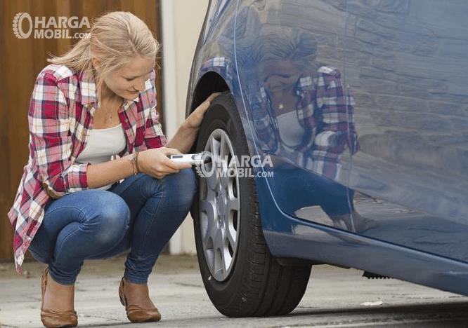 Gambar ini menunjukkan sorang wanita sedang memeriksa tekanan angin ban mobil dengan bodi warna biru