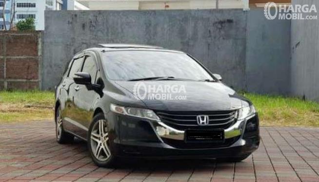 Gambar ini menunjukkan Mobil Honda Odyssey warna hitam tampak depan