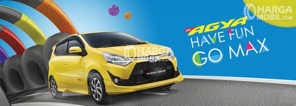 Gambar mobil Toyota Agya berwarna kuning dilihat dari sisi depan