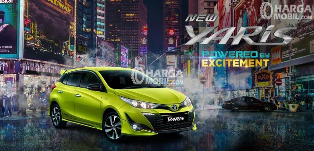 Gambar mobil Toyota Yaris berwarna kuning dilihat dari sisi depan sedang parkir di jalan Indonesia