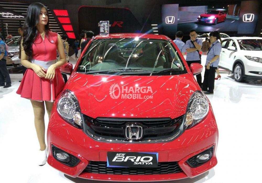 Seorang model sedang berpose disamping Honda Brio Satya warna merah