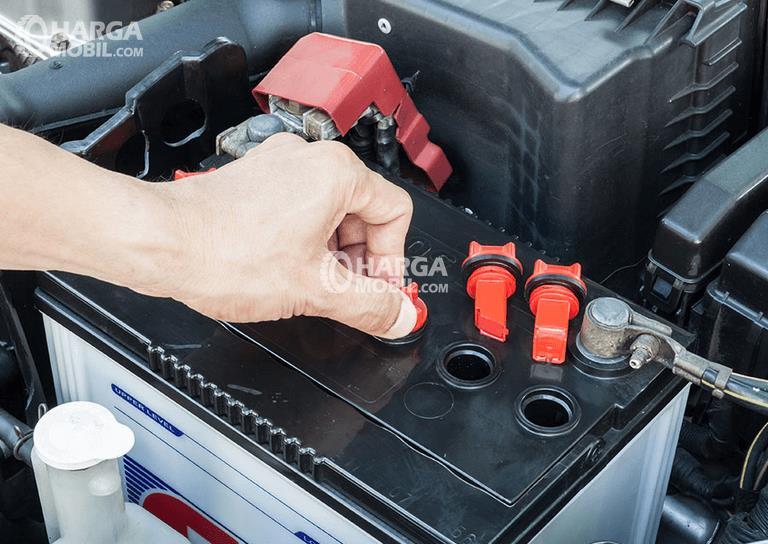 Gambar ini menunjukkan sebuah tangan sedang melepas tutp iki tempat cairan elektrolit warna merah