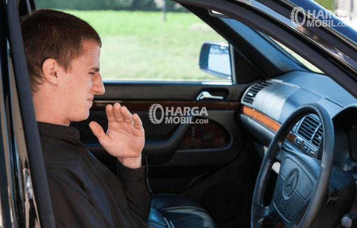Gambar ini menunjukkan seorang pria sedang berada di dalam Mobil dan mencium bau tidak menyenangkan