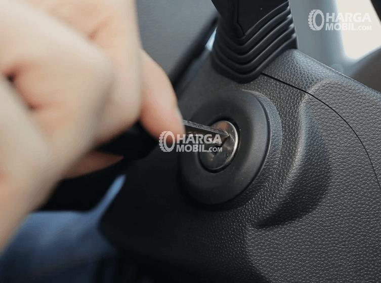 Gambar ini menunjukkan sebuah tangan memegang kunci kontok yang akan dimasukkan ke lubang kontak pada mobil