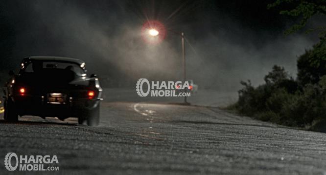 Gambar ini menunjukkan sebuah Mobil berjalan dengan perlahan di malam hari dan terdapat kabut di depannya
