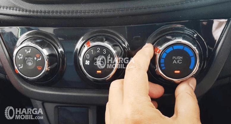 Gambar ini menunjukkan sebuah tangan memegang alat pengatur ac yang terletak di dashboard Mobil