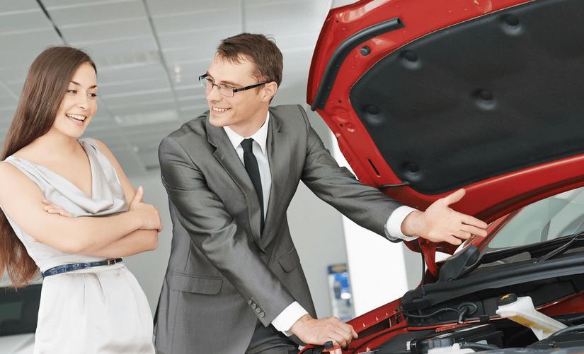 Gambar ini menunjukkan seorang pria dan wanita sedang melihat mesin Mobil warna merah