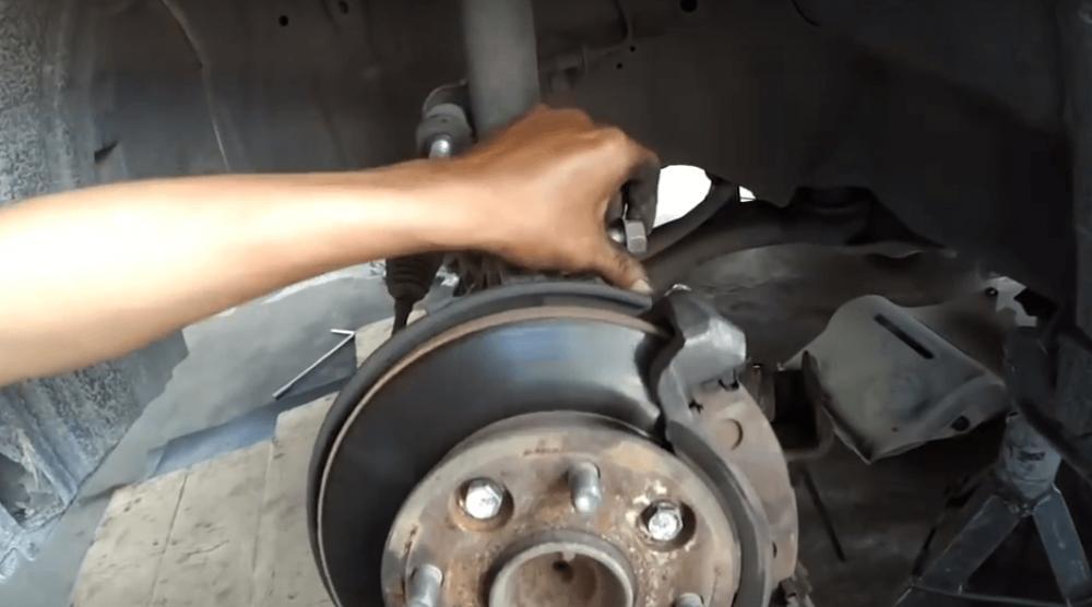 Gambar ini menunjukkan sebuah tangan memegang komponen pada bagian poros roda Mobil Xenia