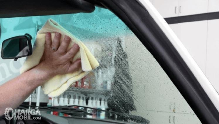 Gambar ini menunjukkan sebuah tangan memegang kanebo dan digosokkan pada kaca Mobil bagian dalam