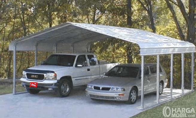 Gambar ini menunjukkan 2 buah Mobil dengan jenis berbeda sedang terparkir di bawah atap