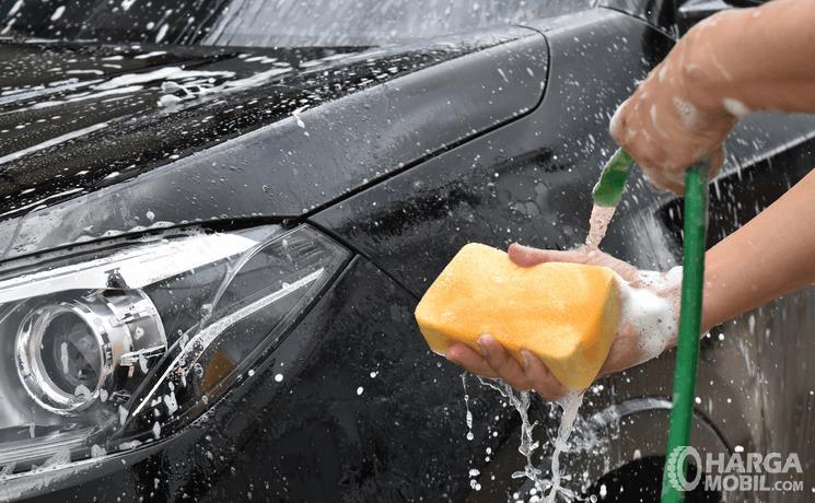 Gambar ini menunjukkan tangan memegang selang air dan busa serta didepannya ada Mobil warna hitam