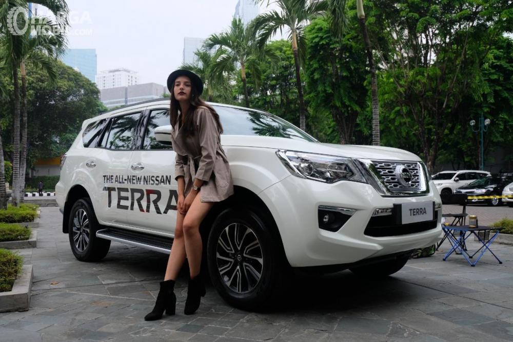 Seorang model berpose bersama Nissan Terra