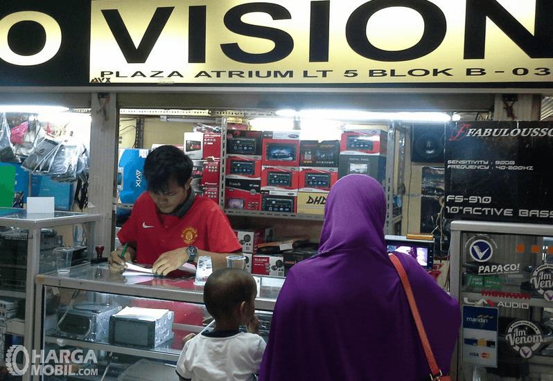 Gambar ini menunjukkan seorang ibu dan anak kecil serta penjual di toko audio Mobil