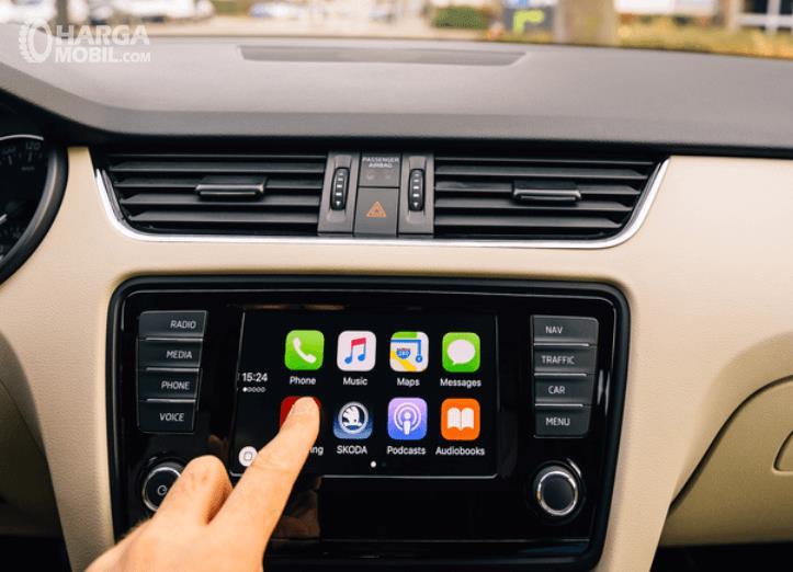 Gambar ini menunjukkan head unit Mobil dan terlihat sebuah jari sedang menunjuk menu pada layar