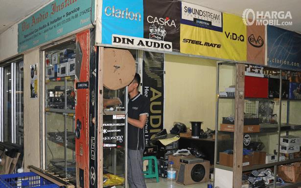 Gambar ini menunjukkan toko audio Mobil dengan seorang penjual di dalamnya
