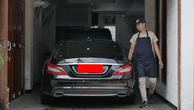 Gambar ini menunjukkan seseorang yang sedang berdiri di dekat Mobil di dalam garasi