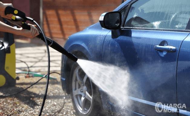 Gambar ini menunjukkan sebuah tangan memegang alat penyemprot air disemprotkan pada Mobil warna biru