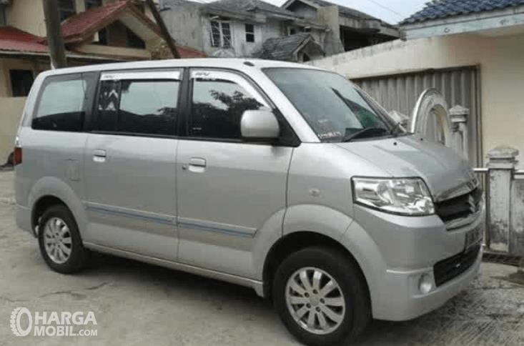 Gambar ini menunjukkan Suzuki APV warna silver sedang terparkir di depan bangunan