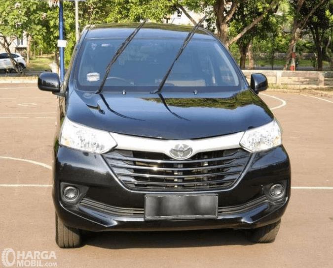 Gambar ini menunjukkan mobil Toyota Avanza warna hitam tampak bagian depan