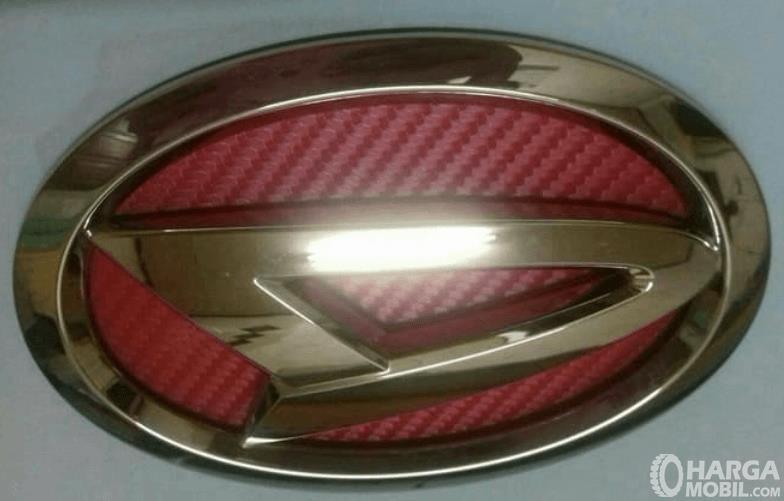Gambar ini menunjukkan logo Daihatsu dengan warna emas dan merah