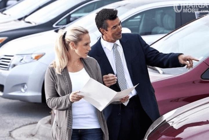Gambar ini menunjukkan 2 orang 1 pria dan 1 wanita sedang melihat mobil
