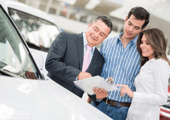 Gambar ini menunjukkan 3 orang sedang melihat selembar kertas di depan mobil warna putih