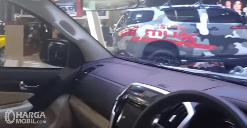 Gambar ini menunjukkan dashboard mobil milik Isuzu MU-X 2018 dan terlihat sedikit bagian dari kemudi mobil