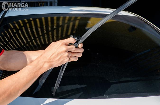 Gambar ini menunjukkan dua buah tangan memgang wiper pada mobil