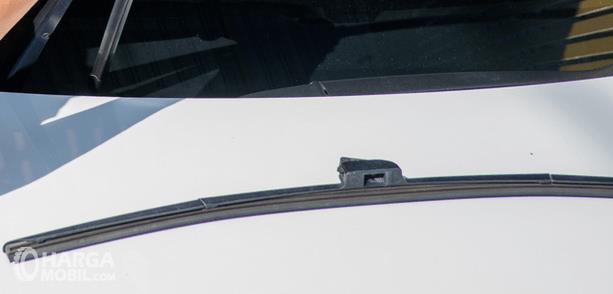 Gambar ini menunjukkan wiper mobil ditempatkan pada atas kap mobil warna putih