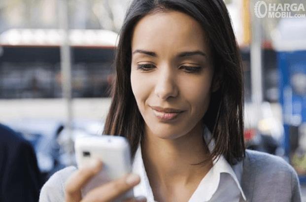 Gambar ini menunjukkan seorang perempuan sedang memegang ponsel
