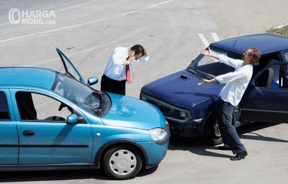 gambar ini menunjukkan 2 buah mobil yang bertubrukan dan 2 orang berdiri di samping mobil masing-masing