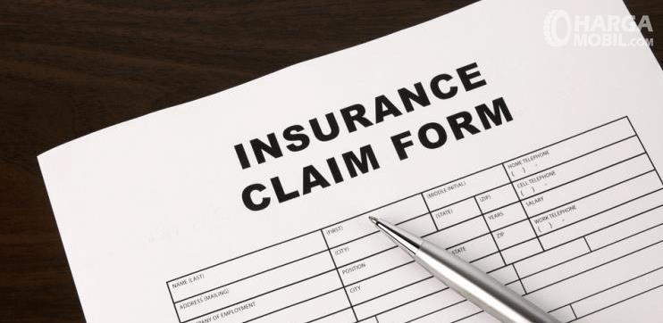 Gambar ini menunjukkan sebuah bolpoin di atas kertas bertuliskan insurance claim form