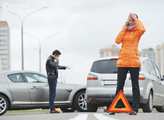 Gambar ini menunjukkan seorang wanita sedang menelpon di belakang mobil dan seorang pria berdiri di samping mobil