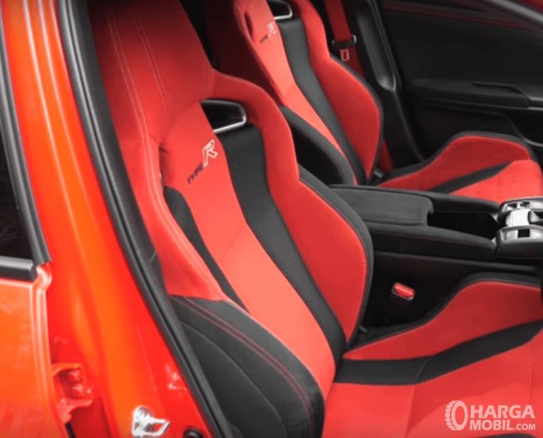 Gambar ini menunjukkan jok mobil dengan perpaduan warna merah dan hitam