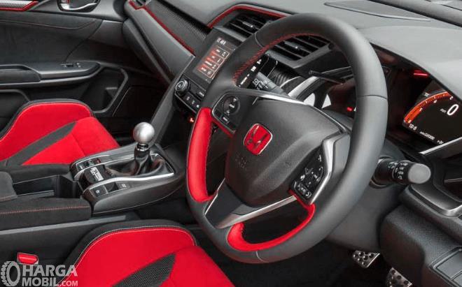Gambar ini menunjukkan kemudi mobil dengan perpaduan warna merah dan hitam serta terdapat beberapa tombol