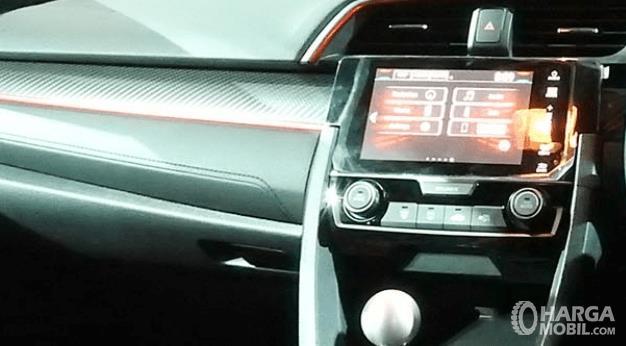 Gambar ini menunjukkan fitur mobil pada dashboard mobil dengan layar di tengahnya